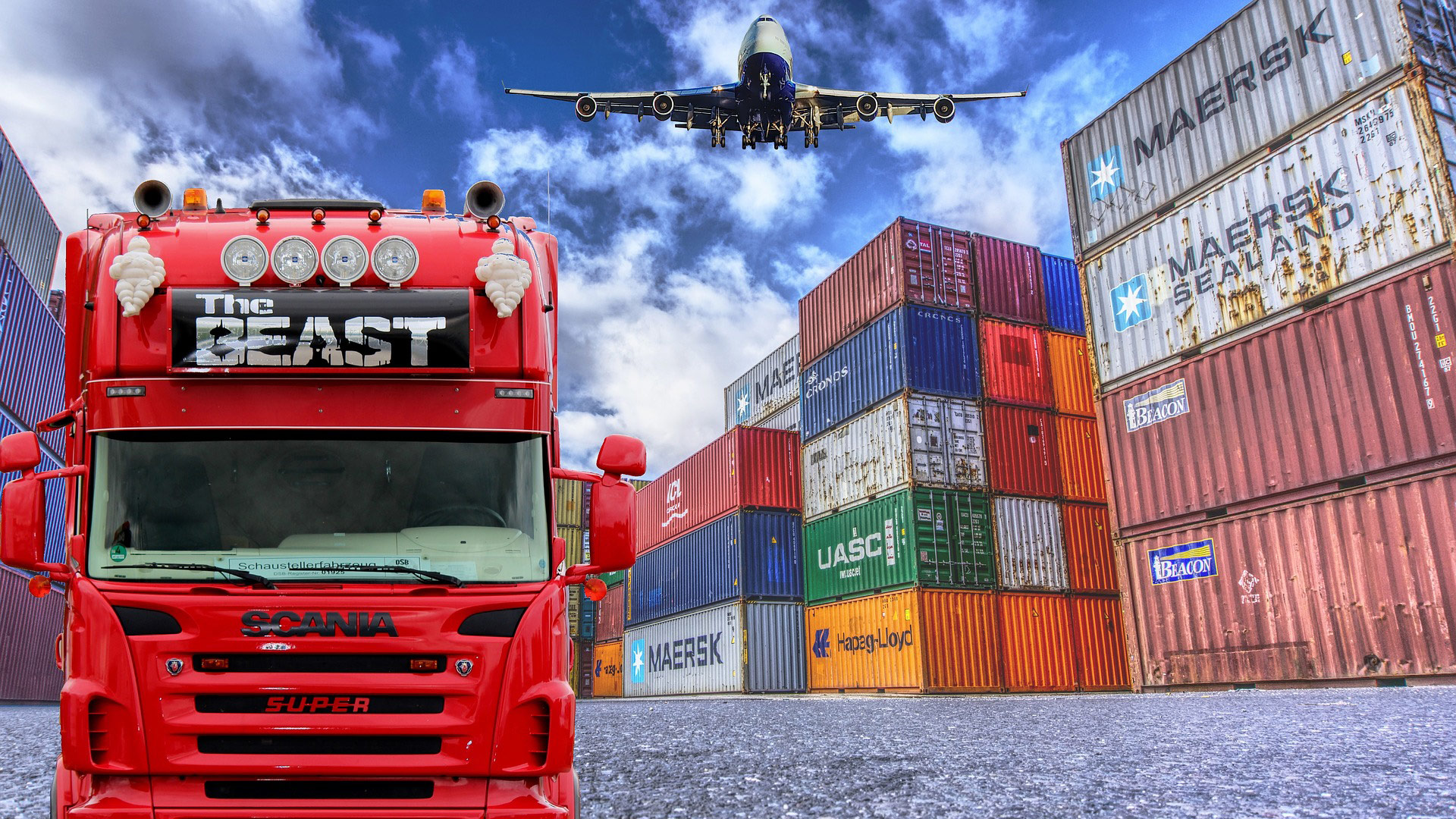 An image depicting common shipping industry vehicles; a red truck and an airplane, as well as shipping containers.