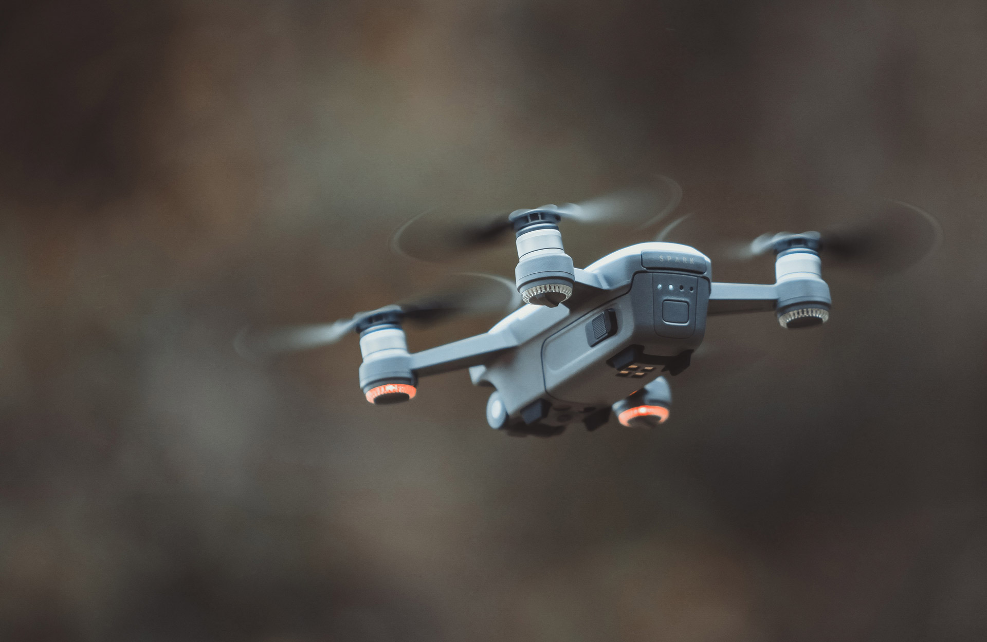 A grey drone flies outdoors.