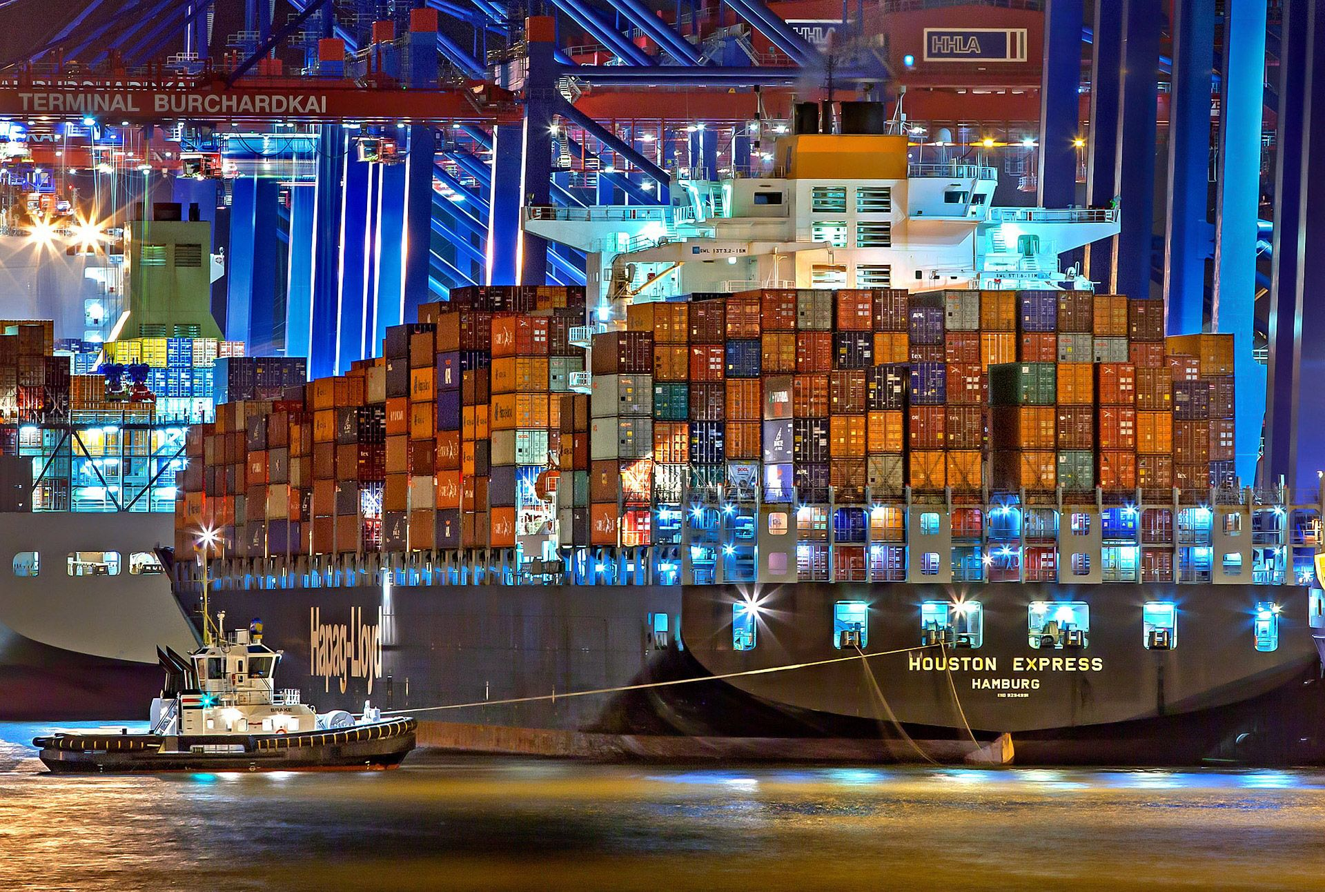 A photo of the 'Houston Express' cargo ship in the port of Hamburg, showing an essential aspect of the supply chain: shipping and logistics.